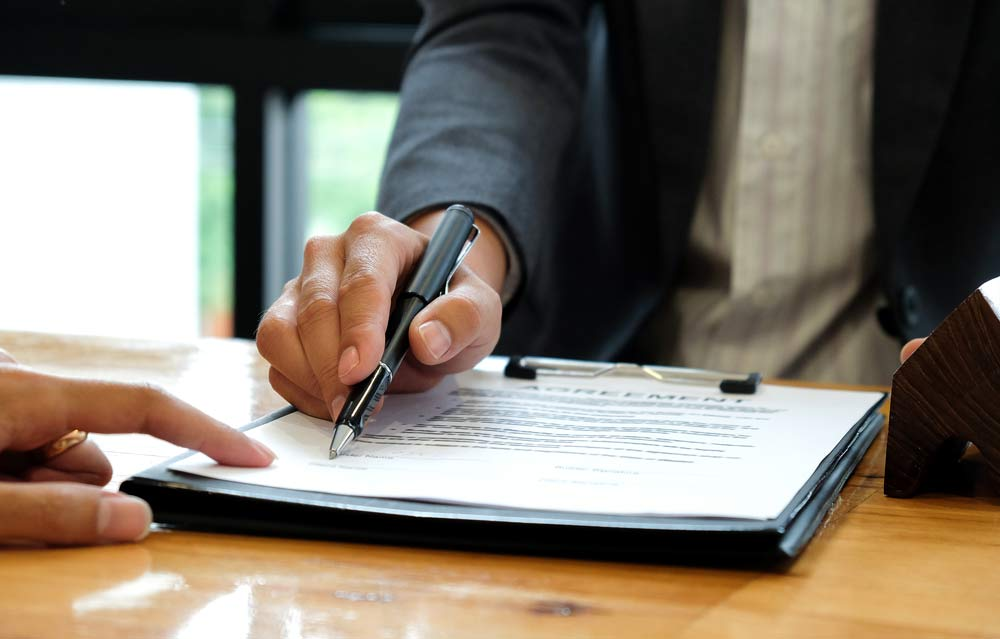 photo of man signing bankruptcy payment plan contract