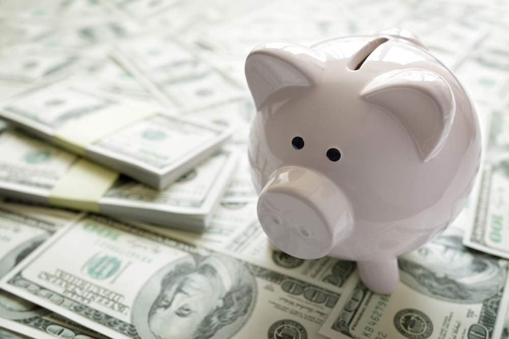 photo of a piggy bank on 100 dollar bills